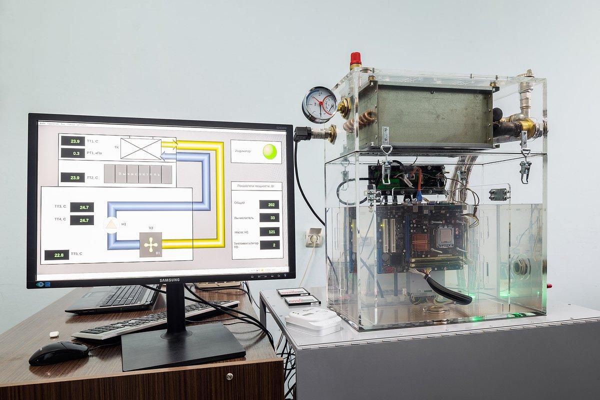 Слева монитор управляющей системы, справа компьютер, на его процессоре заметно кипение.