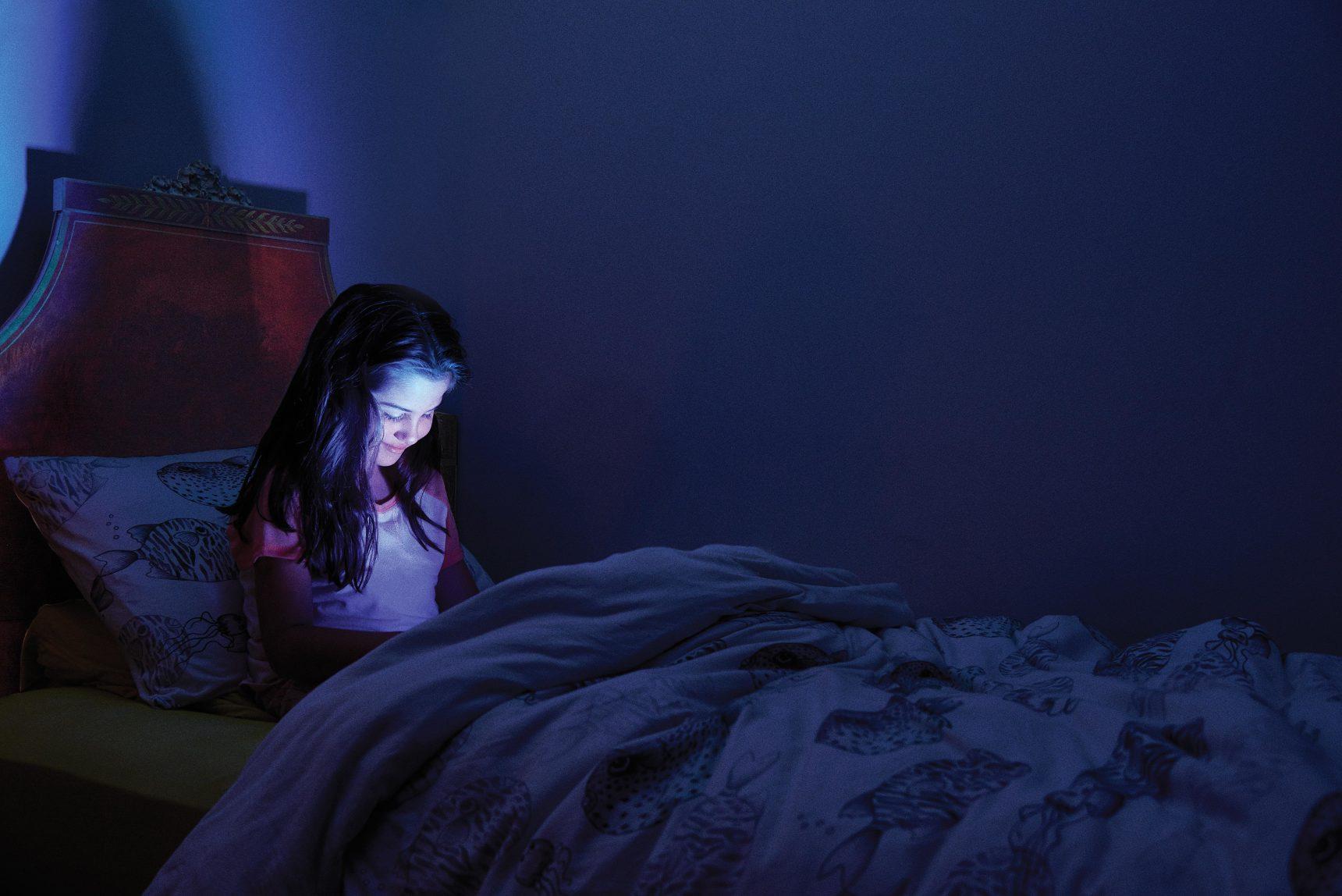 Девочка смотрит мультики под одеялом