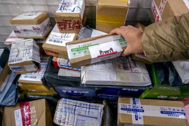 Рабочие готовят товары к отгрузке на складе Cainiao, системы перевозки грузов Alibaba