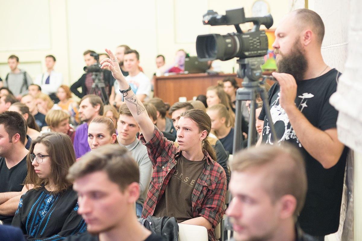 Фотография зала, на которой мужчина тянет руку. Видеооператор рядом с ним работает за профессиональной видеокамерой.