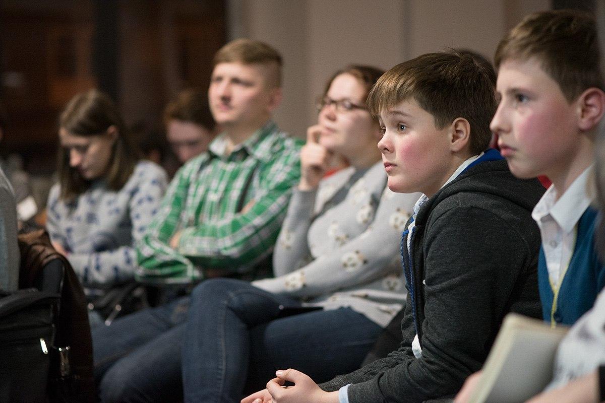 На фотографии слушатели лекции, некоторые из них дети.