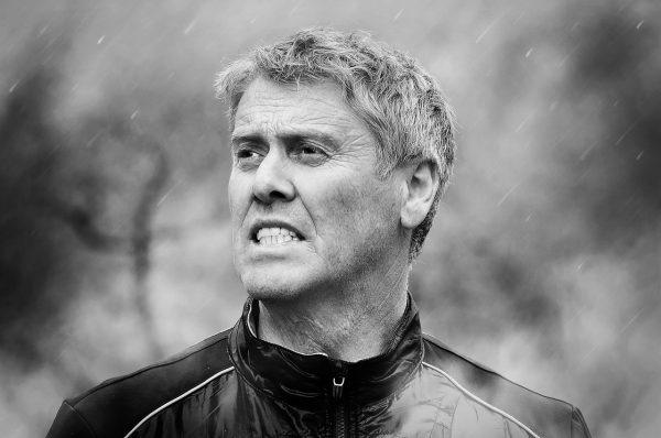 Мужчина среднего возраста напряжённо смотрит через дождь. Чёрно-белая фотография с размытым фоном.