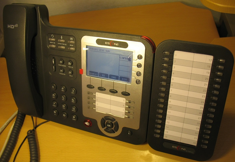 Телефон и модуль расширения на столе